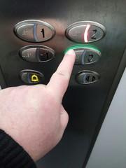 Mano apretando botón de un ascensor