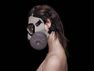 Beautiful girl wearing gas mask profile