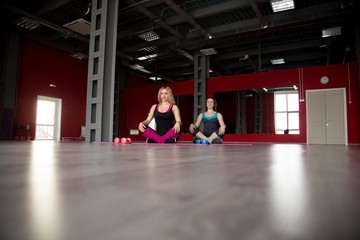 Two pretty girls sit cross-legged on mats in fitness center