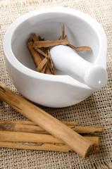mortar and pestle with cinnamon on jute