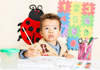 African American black boy drawing at table in kindergarten