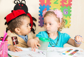 African American black boy and girl drawing in kindergarten