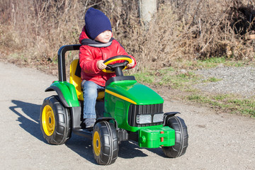 little boy driving toy tractor