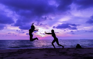 girls having fun by posing on beach during sunset twilight