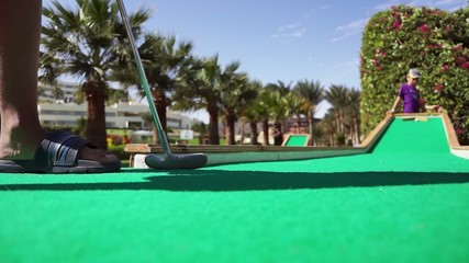 Boy playing mini golf on the background of palm trees