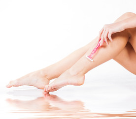 Skin care spa woman shaving legs during bath