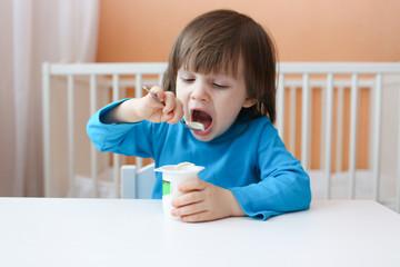 lovely little boy eats youghourt