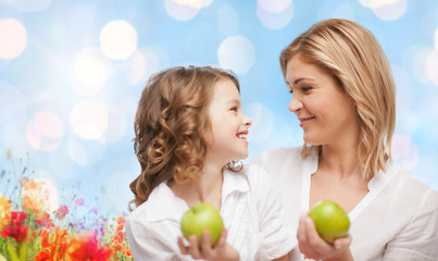 happy mother and daughter with green apples