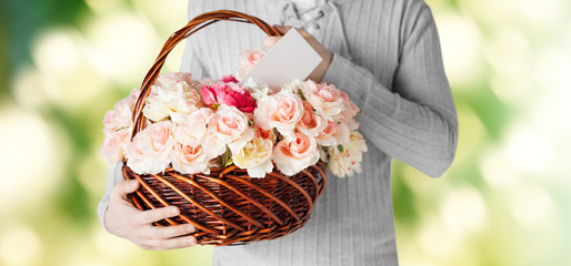 man holding basket full of flowers and postcard