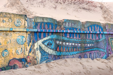 fragment of a concrete wall between the beach and pier