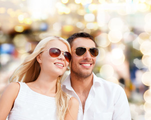 happy couple in shades over lights background
