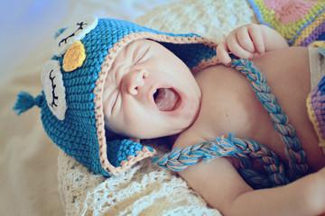 yawning newborn in owl hat