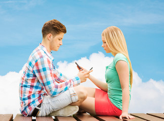 couple with smartphones sitting on bench over sky