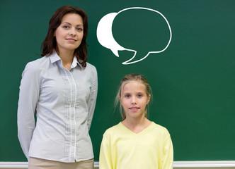 little school girl with teacher at blackboard