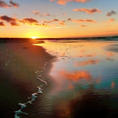 Sunset at sea coast with reflection of sky in water