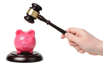 Hand with gavel beats on a piggy bank