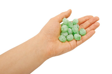 Green mints candy in hand isolated on white background