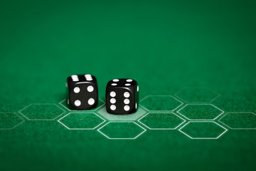 close up of black dice on green casino table