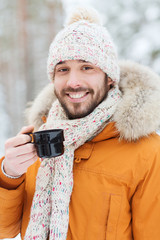 smiling young man with cup in winter forest