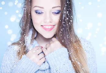 Winter face close up of young woman covered with snow flakes