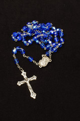 Blue glass rosary isolated on the dark background