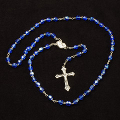 Holy rosary with Christian cross isolated on the dark background