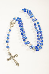 Blue rosary isolated on the bright background