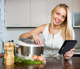 housewife reading ereader and cooking with multicooker
