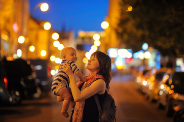 Woman with her little baby at the night city