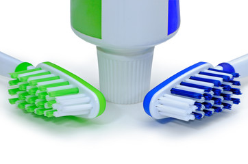 Green, blue toothbrushes and toothpaste isolated on a white back