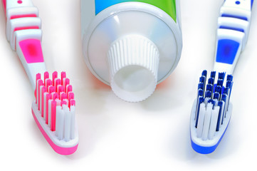 Pink, blue toothbrushes and toothpaste isolated on a white backg