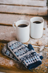Two cups of hot tea on the wooden table in a cold snowy weather