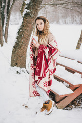 Young woman wrapped in blanket drinking hot tea in snowy forest