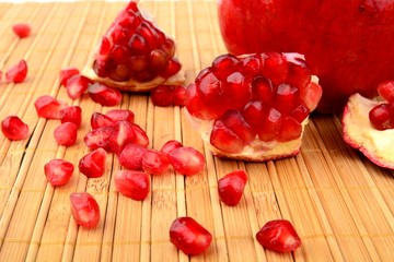 Studio shot open pomegranate on bright wooden mate