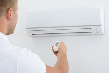 Man Holding Remote Controller Of Air Conditioner