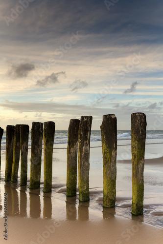 canvas print picture Poteaux sur une plage à Calais