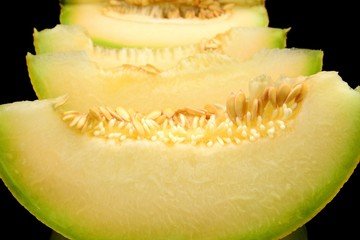 Closeup melon galia slices, pieces isolated black in studio
