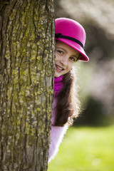 Child peeking behind a tree
