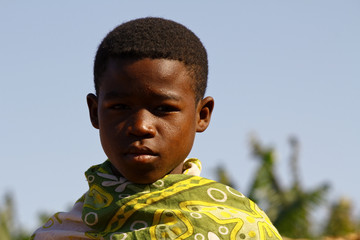 Portrait of adorable young happy boy - african poor child, pover