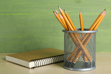 Pencils in metal holder near the notebook