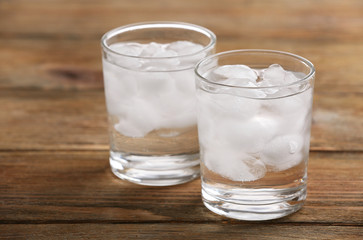 Glasses with ice cubes on wooden table
