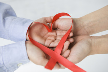 Red ribbon, the hands of the mother and child