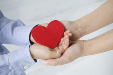The hands of the mother and child that put a red heart