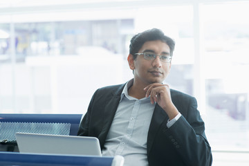 Indian business man having a thought at airport