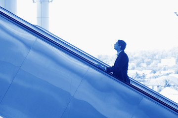Indian businessman ascending escalator