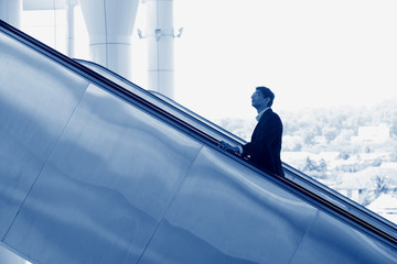 Indian businessman going up escalator