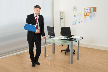 Disabled Businessman Standing With Crutches