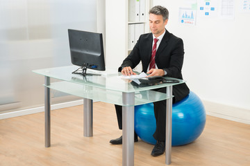 Businessman Working In Office Sitting On Pilates Ball