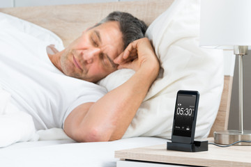 Man On Bed With Alarm On A Cell Phone Display