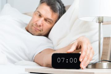 Mature Man Turning Off Clock